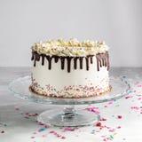 Le gâteau posé d'égouttement d'anniversaire avec le ganache de chocolat et arrose sur un fond blanc avec le décor de partie images stock