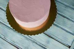 Le gâteau rose est la forme parfaite, couverte de la crème Sur le support Non décoré, après congélation Photos libres de droits