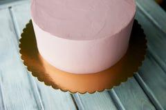 Le gâteau rose est la forme parfaite, couverte de la crème Sur le support Non décoré, après congélation Images libres de droits