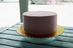 Le gâteau rose est la forme parfaite, couverte de la crème Sur le support Non décoré, après congélation Photo stock