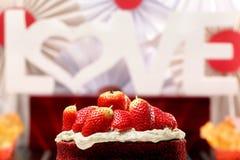 Le gâteau rouge de velours avec des fraises et l'inscription aiment Images libres de droits