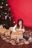 Le gåvor för flickaöppningsjul över rött Royaltyfria Bilder