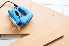 Le gabarit a vu et la feuille en bois sur le plancher Photographie stock libre de droits