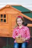 Le galline del selezionatore scherzano l'agricoltore del proprietario di ranch della ragazza con i pulcini in gabbia di pollo Fotografia Stock