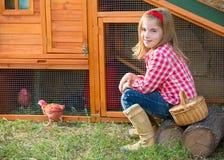 Le galline del selezionatore scherzano l'agricoltore del proprietario di ranch della ragazza con i pulcini in gabbia di pollo Immagini Stock