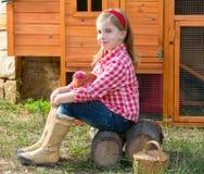Le galline del selezionatore scherzano l'agricoltore del proprietario di ranch della ragazza con i pulcini in gabbia di pollo Immagine Stock