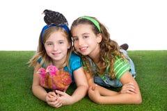 Le galline del selezionatore scherzano le ragazze dell'agricoltore della sorella divertendosi con il 'chi' del pollo Fotografia Stock