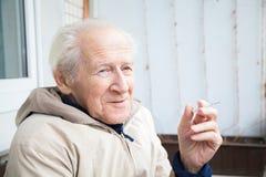 Le gamala mannen med en cigarett royaltyfri fotografi
