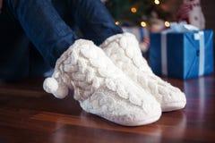Le gambe in calzini caldi si avvicinano all'albero di Natale Immagine Stock