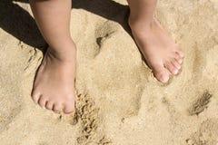 Le gambe dei bambini stanno sulla spiaggia con lo spazio della copia fotografia stock libera da diritti