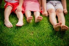 Le gambe dei bambini sull'erba gambe nude delle bambine che si siedono sul prato i bambini si siedono sull'erba con le gambe nude immagini stock