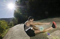 Le gambe del corridore con il sole si accendono in sentiero forestale Immagine Stock