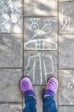 Le gambe del ` delle ragazze con le scarpe di una porpora sulla pavimentazione con gesso disegnano Fotografie Stock Libere da Diritti
