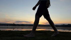 Le gambe del giovane vanno lungo un lago ad un tramonto splendido nel slo-Mo video d archivio
