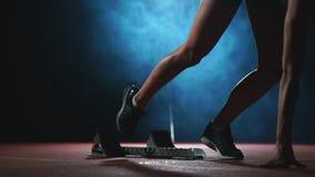 Le gambe del primo piano dell'atleta si avvicinano alla pedana mobile e diventano nella posizione per iniziare la corsa video d archivio