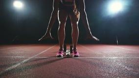 Le gambe del primo piano dell'atleta si avvicinano alla pedana mobile e diventano nella posizione per iniziare la corsa stock footage
