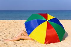 Le gambe del ` s delle donne eleganti guardano fuori da sotto l'ombrello variopinto Immagine Stock