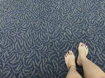Le gambe del ` s del viaggiatore che indossa braccialetto di caviglia è disposta sulla sedia vicino dai suoi bagagli fotografia stock libera da diritti