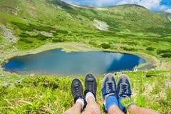 Le gambe del viaggiatore che si siedono sull'alta montagna completano nel viaggio Immagini Stock Libere da Diritti