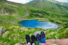Le gambe del viaggiatore che si siedono sull'alta montagna completano nel viaggio Immagini Stock