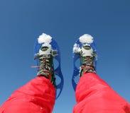 Le gambe dell'alpinista con le racchette da neve Immagine Stock