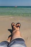 Le gambe dell'uomo che si rilassano alla spiaggia Fotografia Stock