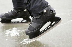 Le gambe dell'uomo di un pattinatore alla pista di pattinaggio fotografia stock libera da diritti