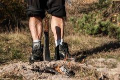 Le gambe dell'uomo forte, stando dietro il fuoco del burnig ed il machete attaccati nella terra fotografie stock libere da diritti