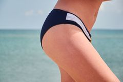 Le gambe della bella donna sul fondo del mare Giorno di estate piacevole fotografia stock
