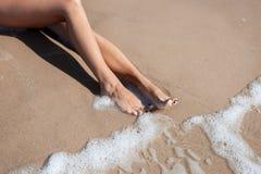 Le gambe della donna alla spiaggia sabbiosa Immagini Stock Libere da Diritti