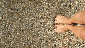 Le gambe della donna che stanno in acqua di mare blu ondeggia la scavatura nella sabbia Vista personale stock footage