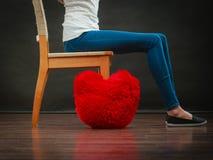 Le gambe della donna con cuore rosso appoggiano sul pavimento Fotografia Stock