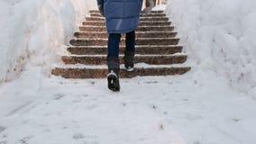 Le gambe della donna del primo piano che aumentano su su una scala nevosa, scala Parco di inverno nella città durante il giorno i video d archivio