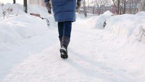 Le gambe della donna del primo piano sta camminando nel parco dell'inverno nella città durante il giorno in tempo nevoso con neve archivi video