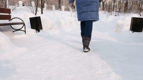 Le gambe della donna del primo piano sta camminando nel parco dell'inverno nella città durante il giorno in tempo nevoso con neve stock footage