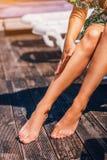 Le gambe della donna sullo stagno di Chaise Lounge In The Swimming immagini stock