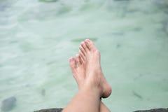 Le gambe della giovane donna che si siedono sulla spiaggia e sulla gamba dell'incrocio con acqua sono b Immagine Stock