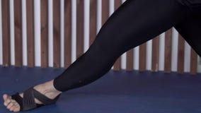 Le gambe della giovane donna che sta facendo yoga si esercita nella classe, fine su archivi video