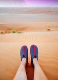 Le gambe della persona che si siedono sulla sabbia arancio del Wahiba abbandonano, l'Oman Fotografia Stock