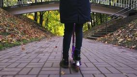 Le gambe della ragazza del bambino stanno guidando sul motorino sul marciapiede nel parco di autunno colpo dello steadicam archivi video