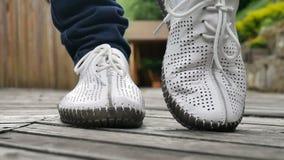 Le gambe della ragazza in scarpe bianche sul fondo di legno scuro del pavimento Pantaloni a vita bassa o concetto casuale stock footage