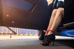 Le gambe delle donne che attaccano dalla finestra di automobile Immagine Stock