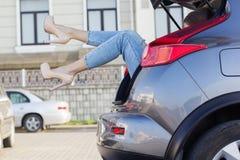 Le gambe delle ragazze nel tronco di automobile sta indossando i talloni Fotografia Stock