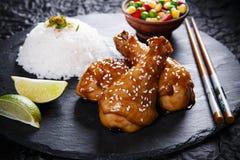 Le gambe di pollo fritto con il teriyaki sauce i semi di sesamo ed il riso sulla pietra nera Fotografia Stock