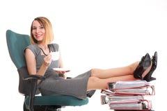 Le gambe di rilassamento della donna di affari di sciopero della donna aumentano l'abbondanza del documento Immagine Stock