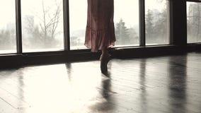 Le gambe di una ballerina nel pointe calza il primo piano Siluetta di una ballerina contro lo sfondo di grande finestra lento stock footage