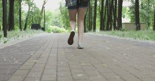 Le gambe di una giovane donna che cammina nel parco stock footage