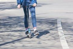 Le gambe di una ragazza sconosciuta in scarpe da tennis bianche e jeans stretti guidano su un motorino elettrico nero sopra un as fotografie stock libere da diritti