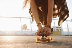 Le gambe e le mani della ragazza dei pantaloni a vita bassa con gli anelli su un pattino imbarcano Fotografia Stock