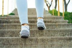 Le gambe femminili in jeans e scarpe da tennis, scalano le scale concrete fuori fotografie stock